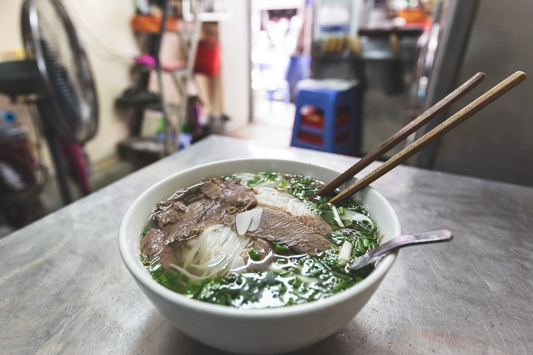 A bowl of pho sits on a table at Pho Bo Hang Dong in Hanoi, Vietnam