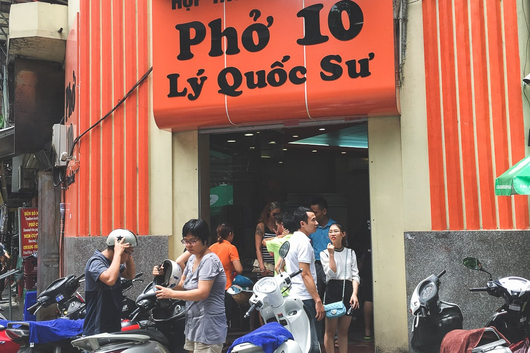 People near their scooters are gathered at Pho 10 Ly Quoc Su in Hanoi