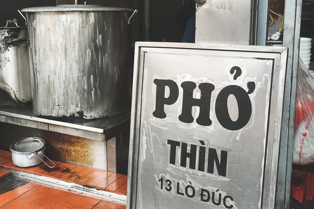 The sign at the entrance to Pho Thin in Hanoi sits next to a pho pot