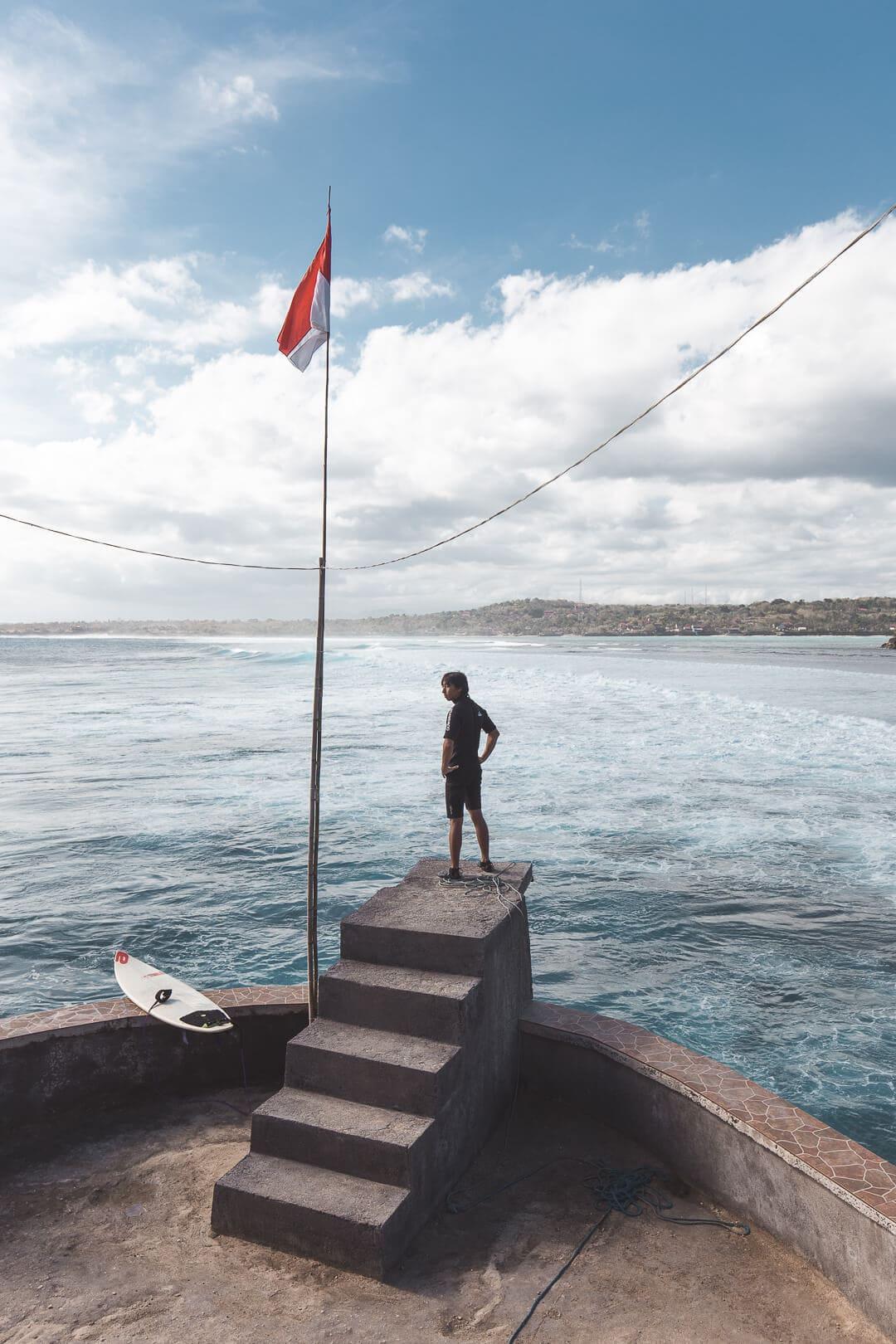 A surfer stands on the jump platform at Mahana Point on Nusa Ceningan Island