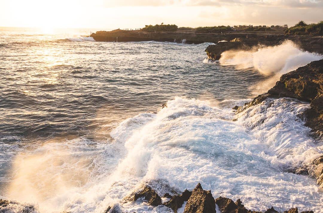 Waves crash on the rocks at Devil's Tear at sunset on Nusa Lembongan Bali