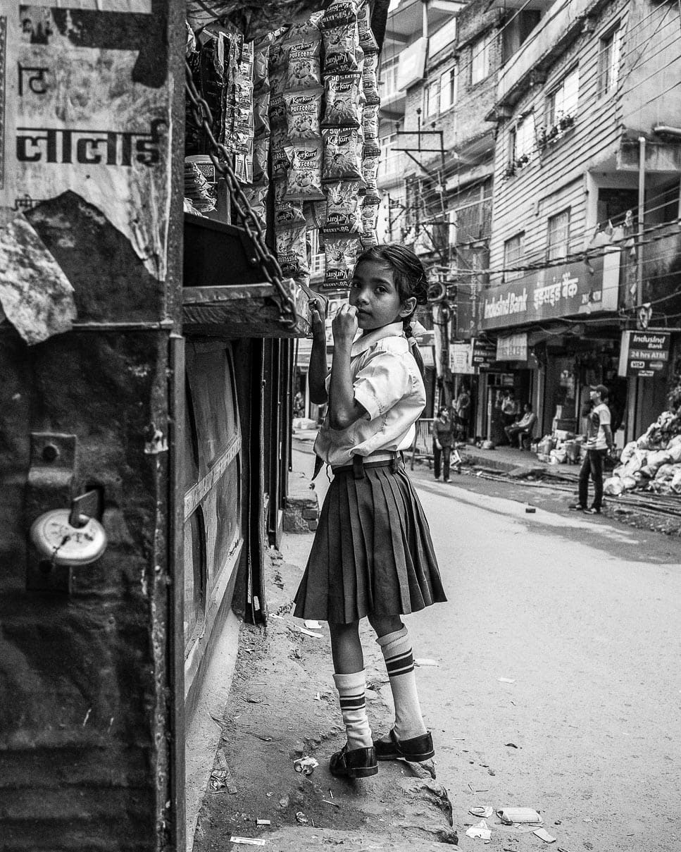 A schoolgirl stops to buy candy at a local shop in Kalimpong, India