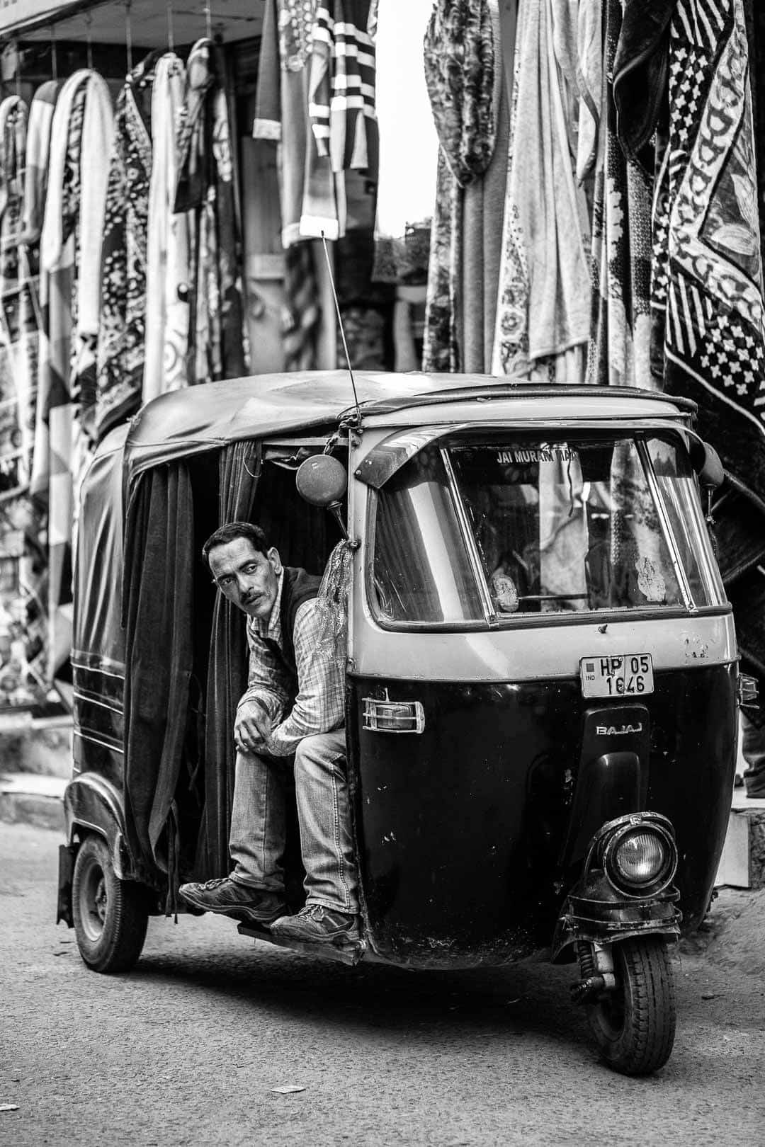 A man sits in his auto-rickshaw in Vashist, India