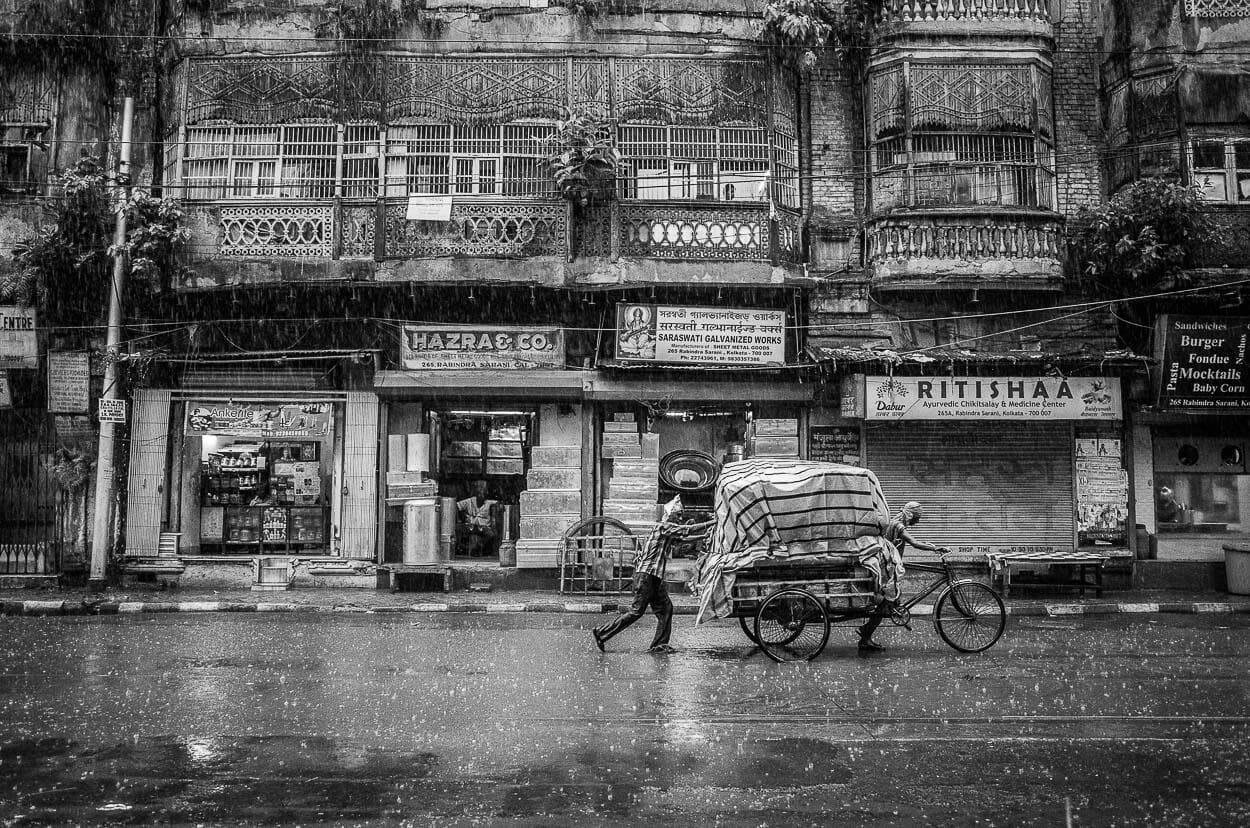 Two men push a cart through the rain in Kolkata, India