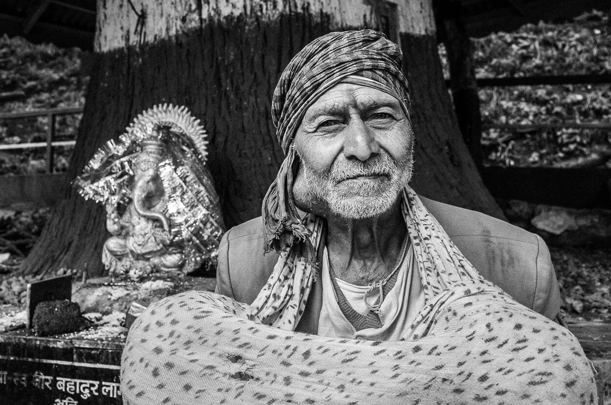 A black and white portrait of a local man sitting outside of Mahakal Mandir temple in Darjeeling