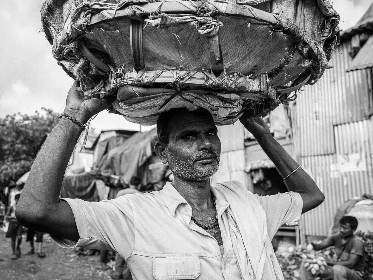 A man carries a basket through the Mallik Ghat flower market in Kolkata, India