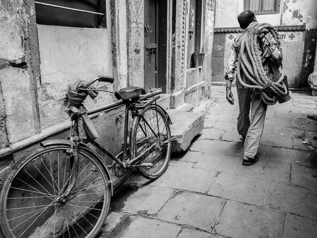 A man carries a rope through the alleys of Varanasi, India