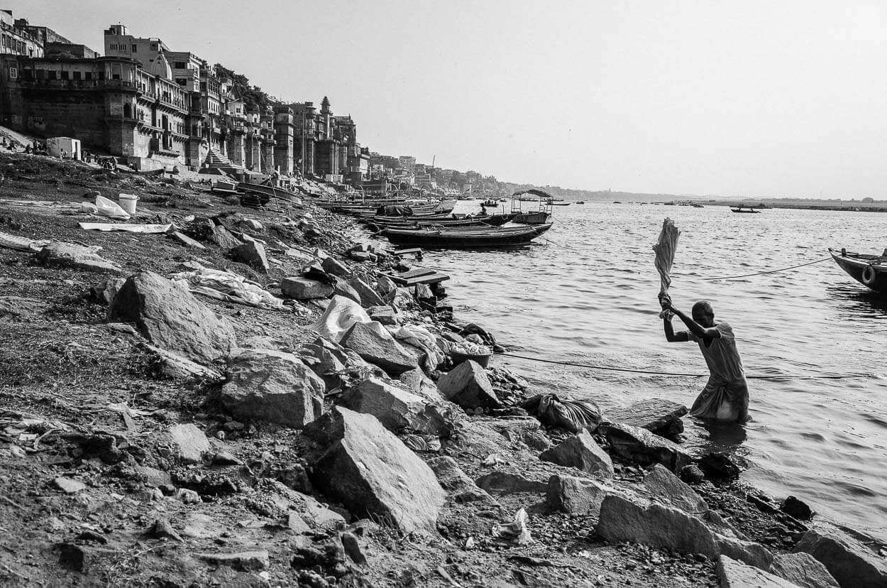 A man doing laundry in the Ganges River in Varanasi, India