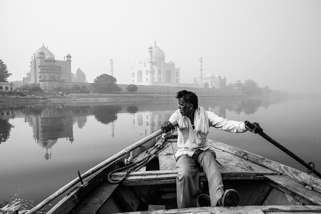 A man rows his boat near the Taj Mahal on the Yamuna River in Agra