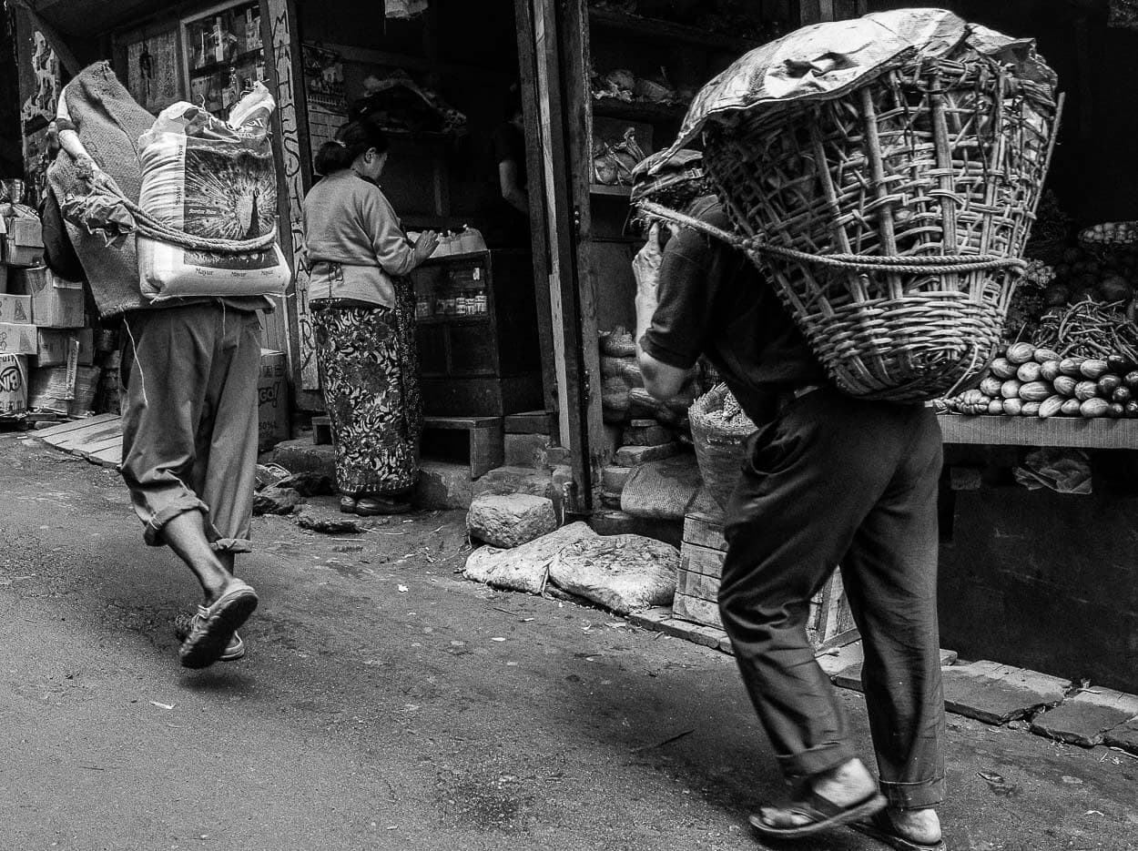 Two laborers carry baskets through Darjeeling, India