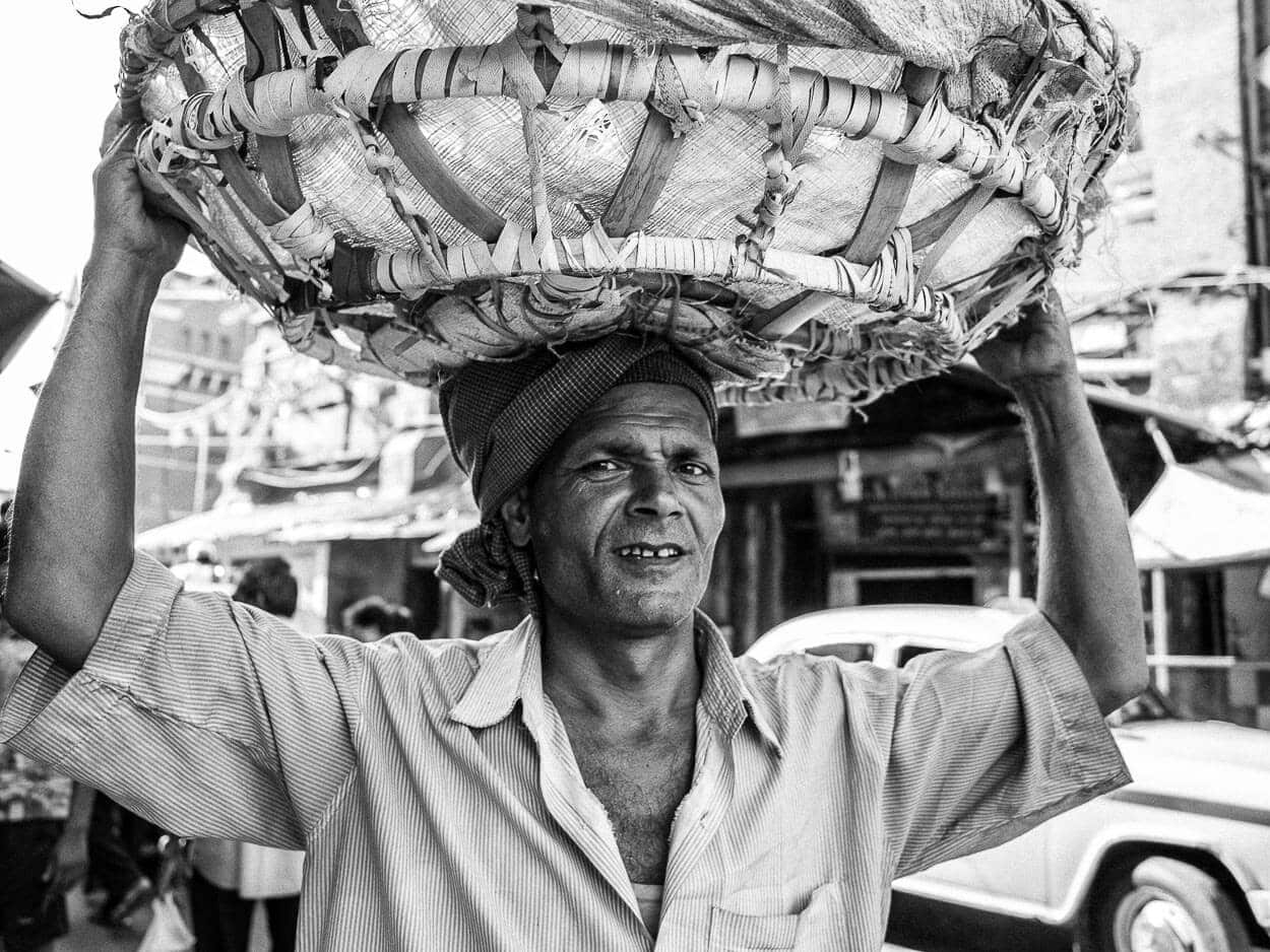 A local laborer carries a basket on his head through New Market in Kolkata, India