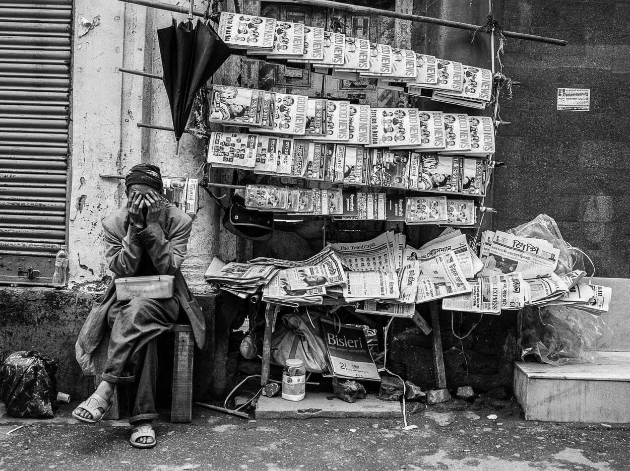 A man sits at a newspaper stand with his hands on his face in Darjeeling, India