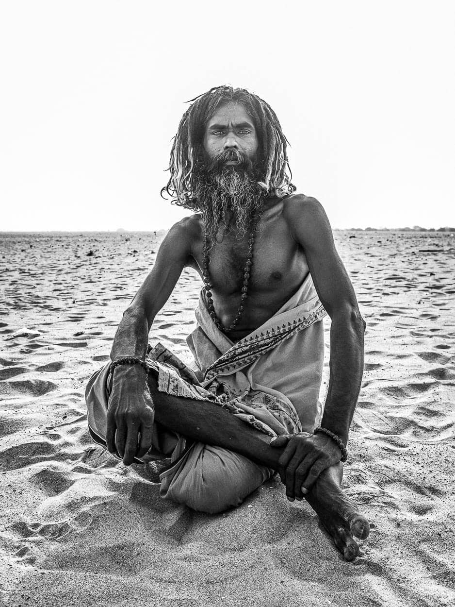 A traveling sadhu sits in the sand near the banks of the Ganges River in Varanasi, India