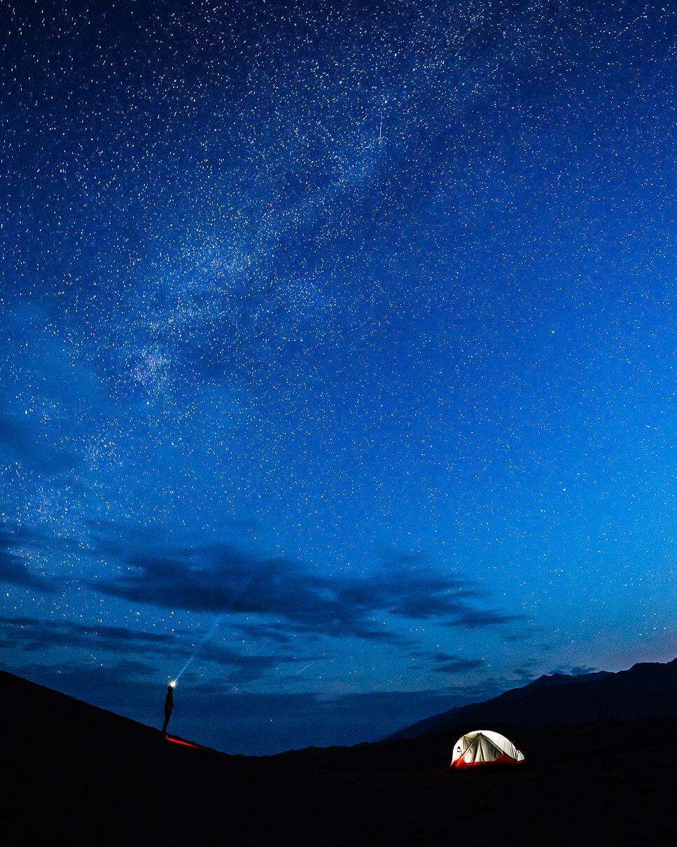 A man stands with a headlamp at night looking at the milky way in Colorado