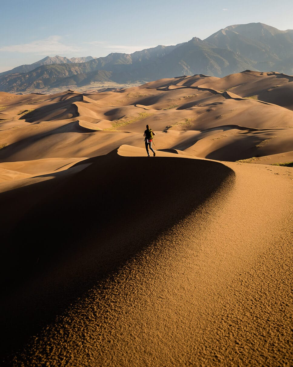 A man walks along the ridges of the sand dunes in Alamosa, Colorado USA