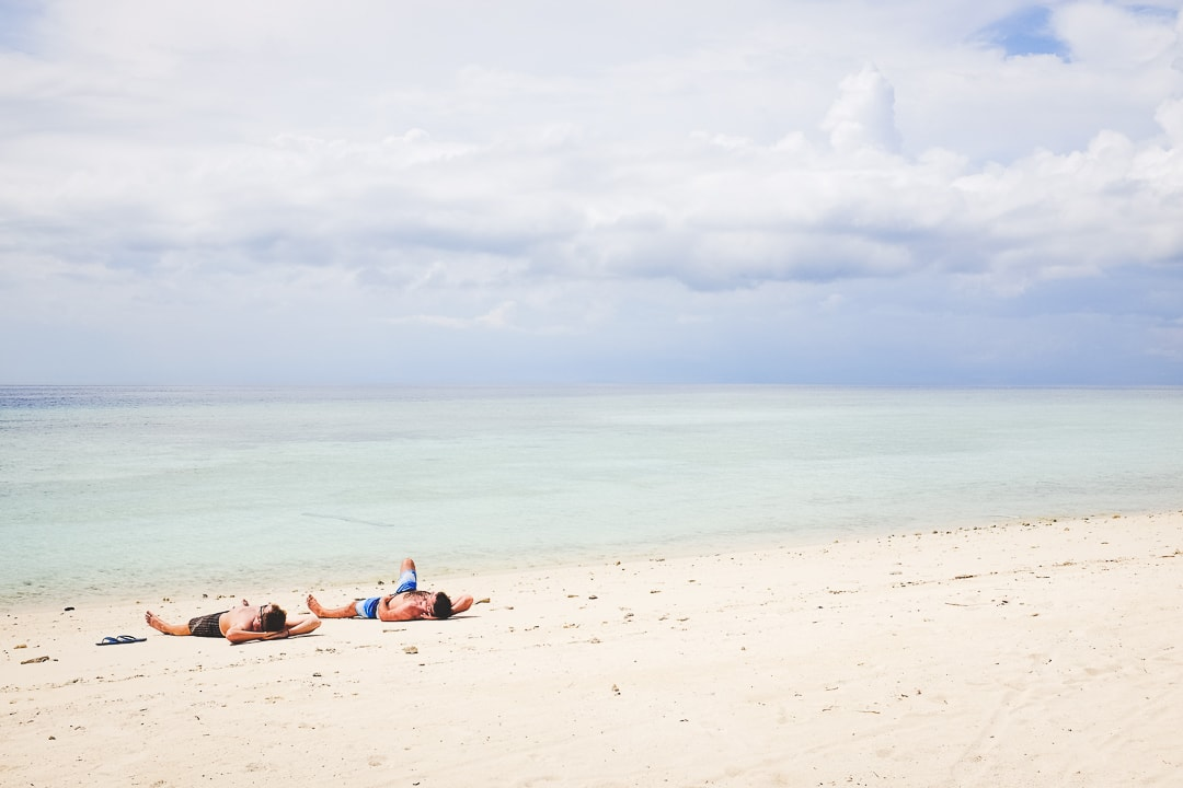 Two guys lay on the white sands of Pom Pom Island beach in Borneo, Malaysia