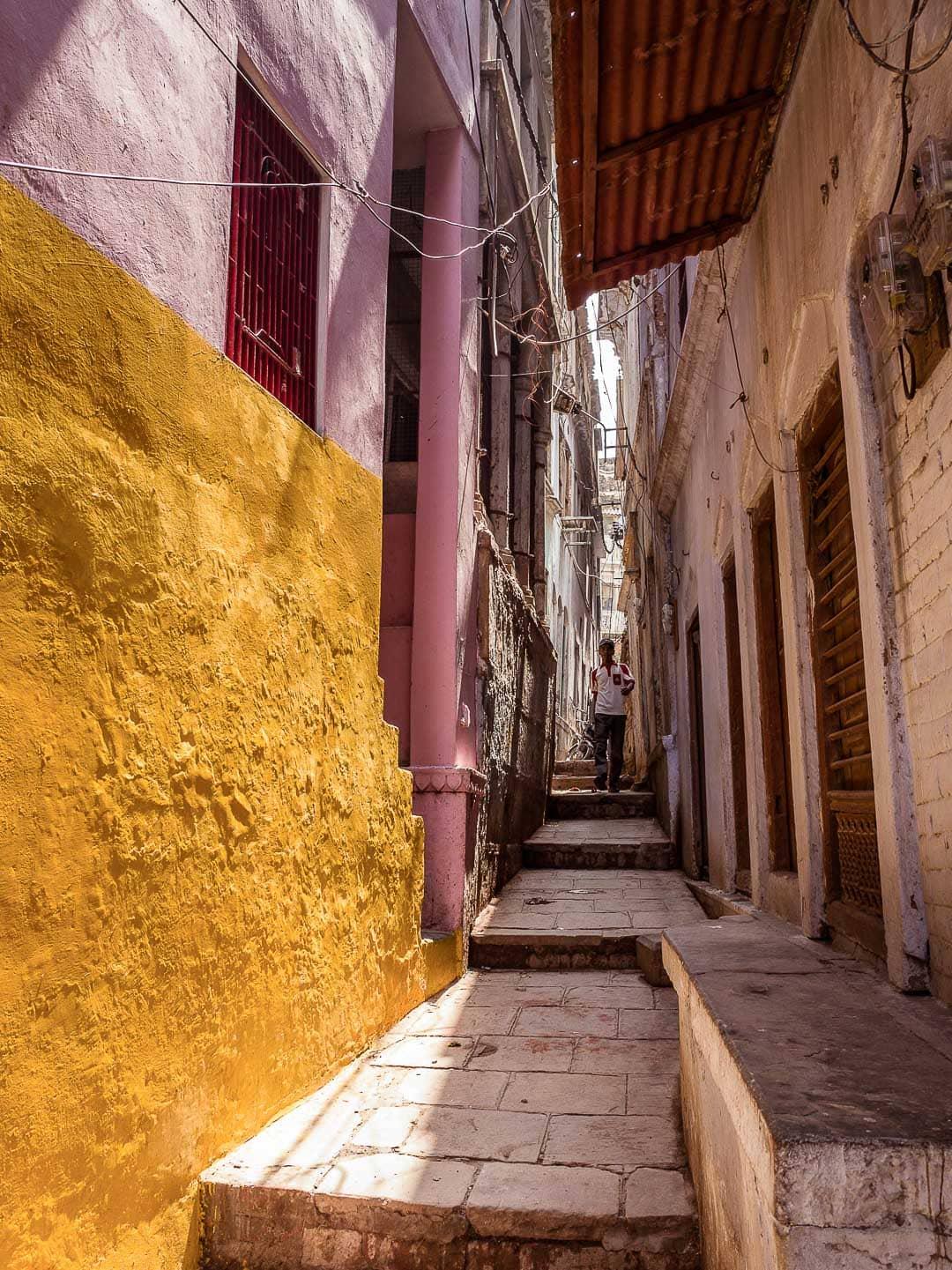 A man walks down a colorful alleyway in Varanasi India