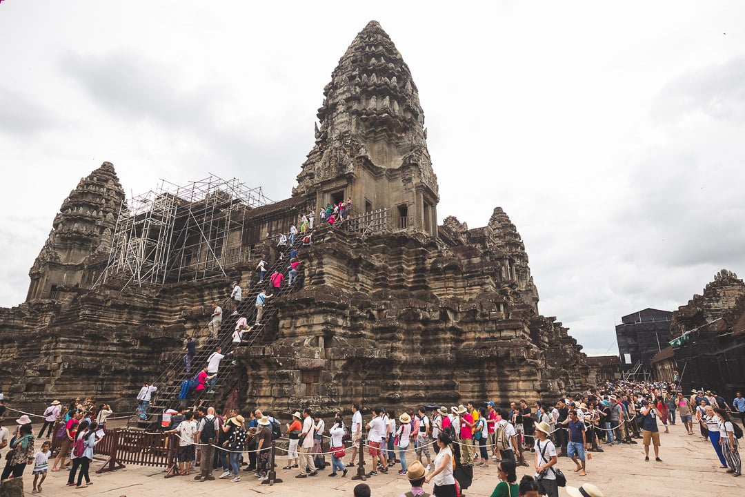 A crowd of tourists lines up at Angkor Wat. How to Avoid Tourists at Angkor.