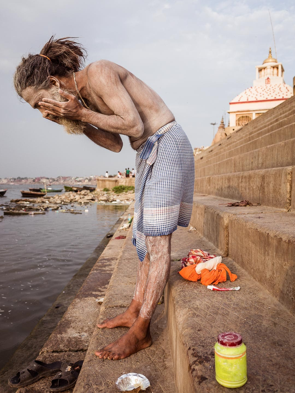 Sadhu covers himself in powder at sunrise along the ghats of Varanasi