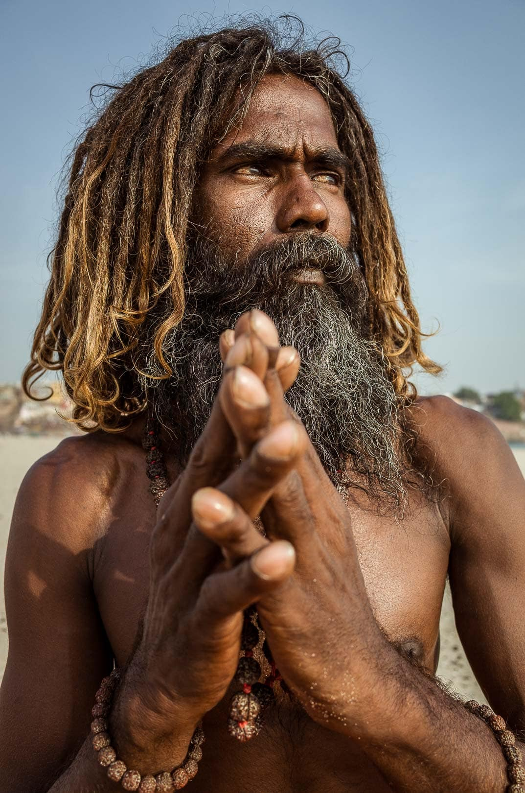 A Sadhu holds his hands together and looks towards the sun in Varanasi, India