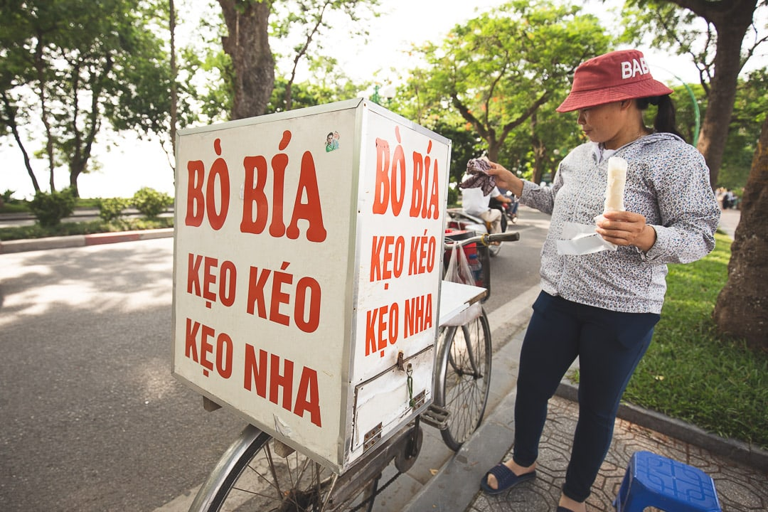 A woman on a bike sells bo bia ngot a dessert commonly found in Hanoi, Vietnam