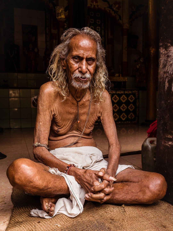 An elder Brahmin man sits near his door in Varanasi, India