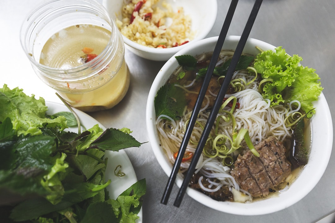 A bowl of Bun Cha with herbs and garlic. Vietnamese foods you must try in Hanoi.
