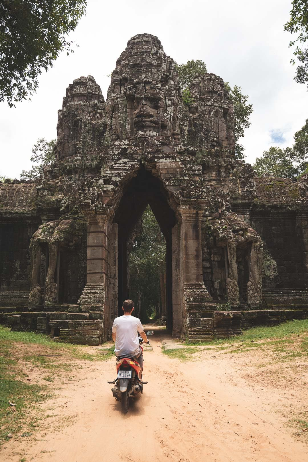Riding a scooter through the death gate inside Angkor Archaeological Park