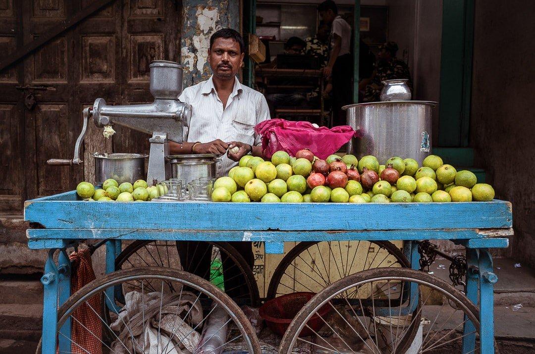 A man stands behind a fruit juice cart in Varanasi, India