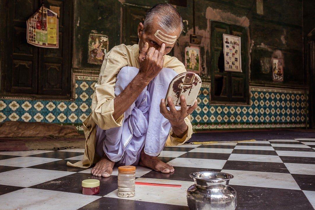A local Hindu man applies tilak to his forehead at a temple in Varanasi