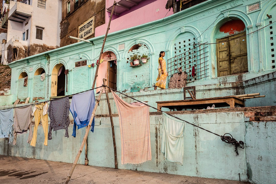 A woman walks near her colorful home near the Lal Ghat in Varanasi, India