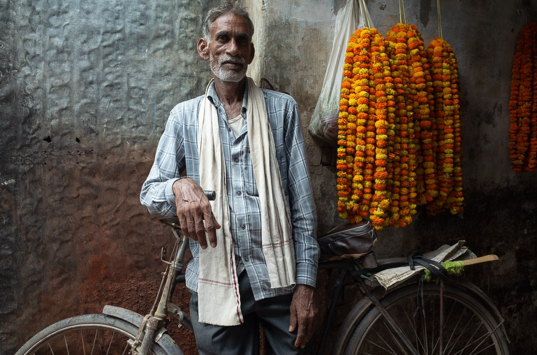 A man leans on a bike next to marigolds at a market in Varanasi, India