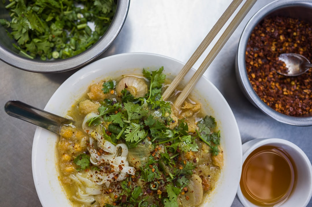 Bowl of Mohinga with green onion, chili flakes, and tea in Yangon, Myanmar