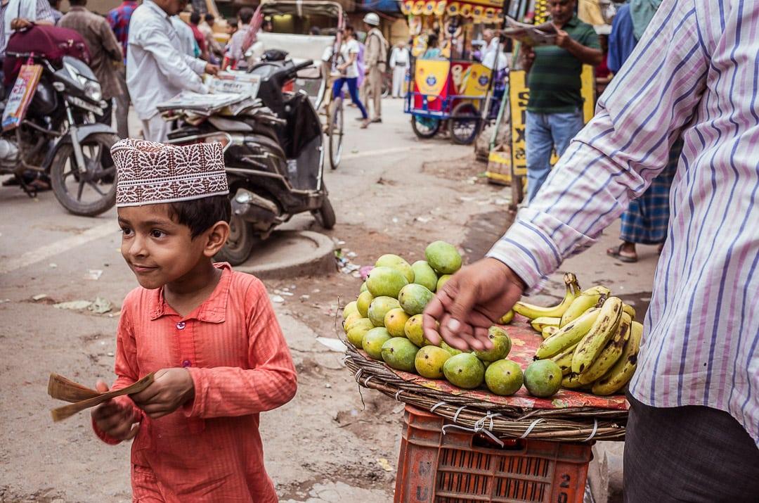 A young Muslim boy buys mangoes in Varanasi, India