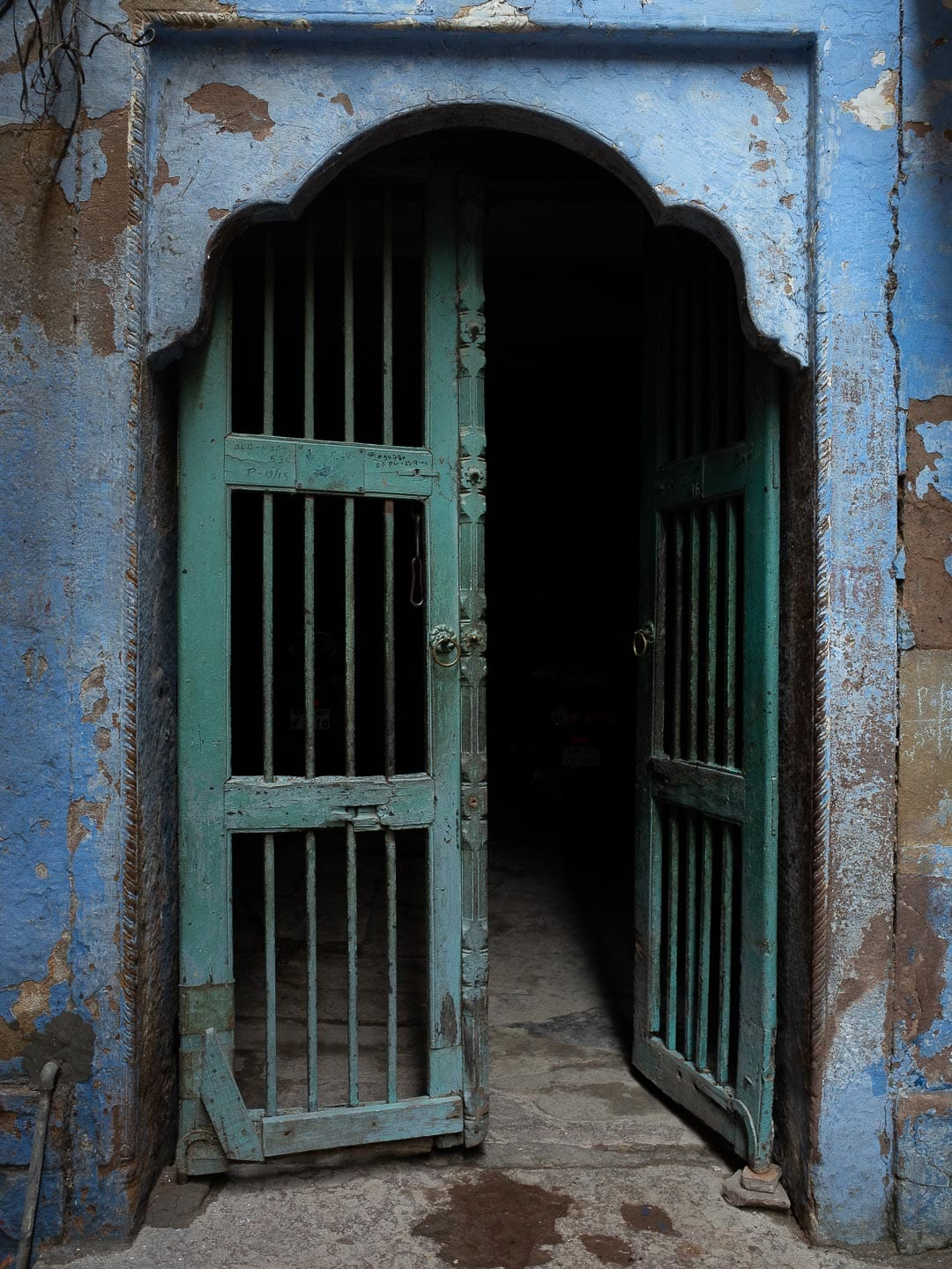 An old blue and green gate in Varanasi, India