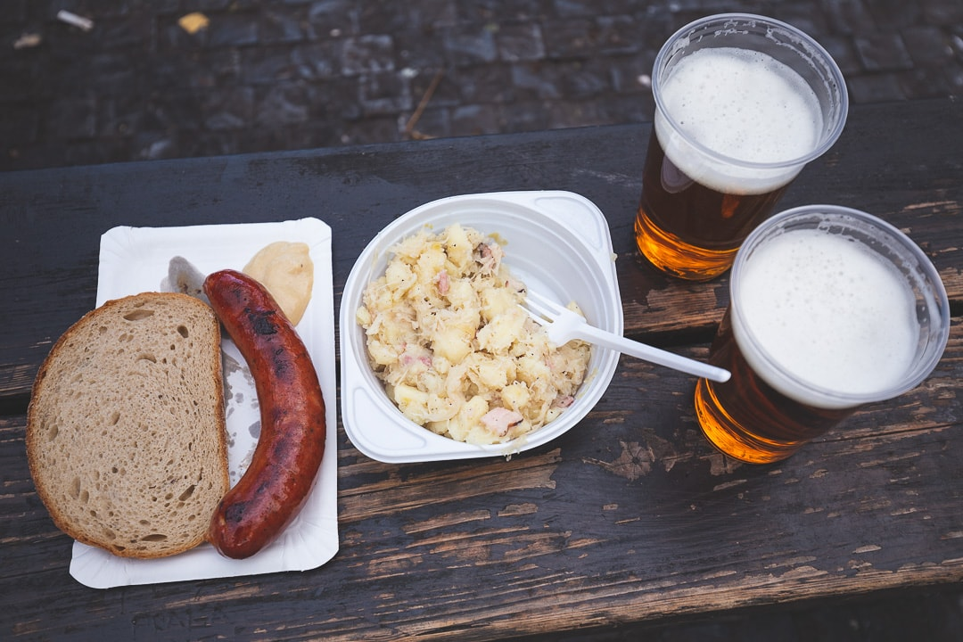 Prague street food including sausage, potatoes and sauerkraut and beer
