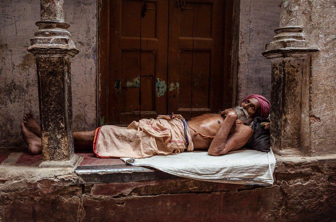 A resting baba laying down in the galis of historic Varanasi