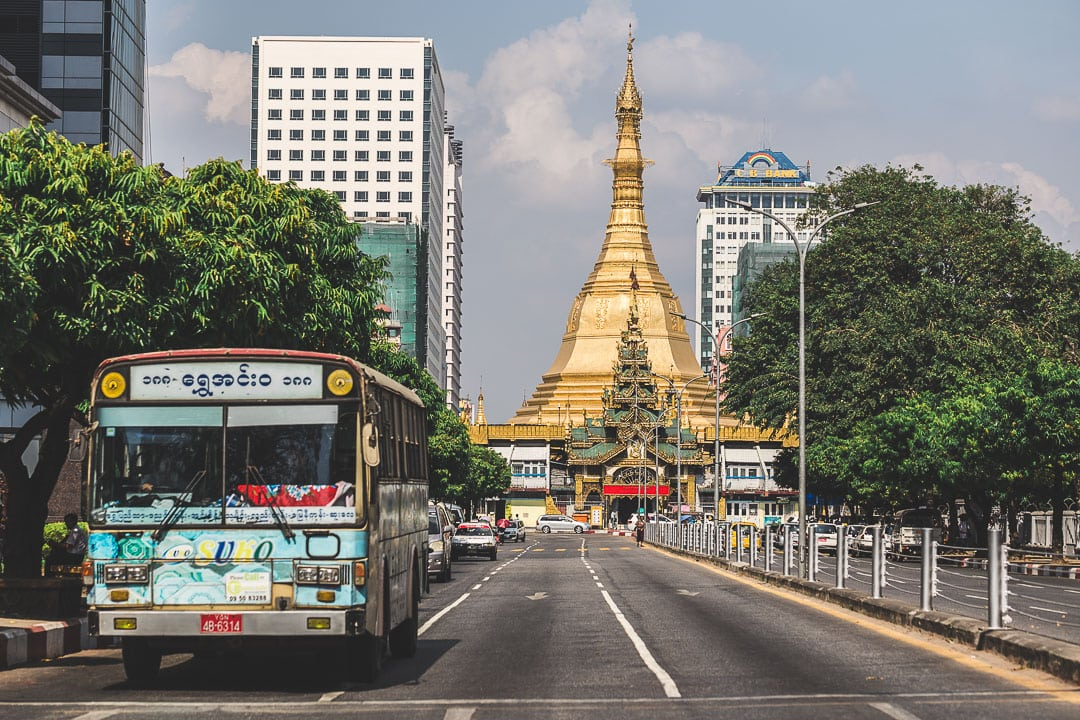 A bus stops in Yangon, Myanmar with a view of Sule Pagoda behind it