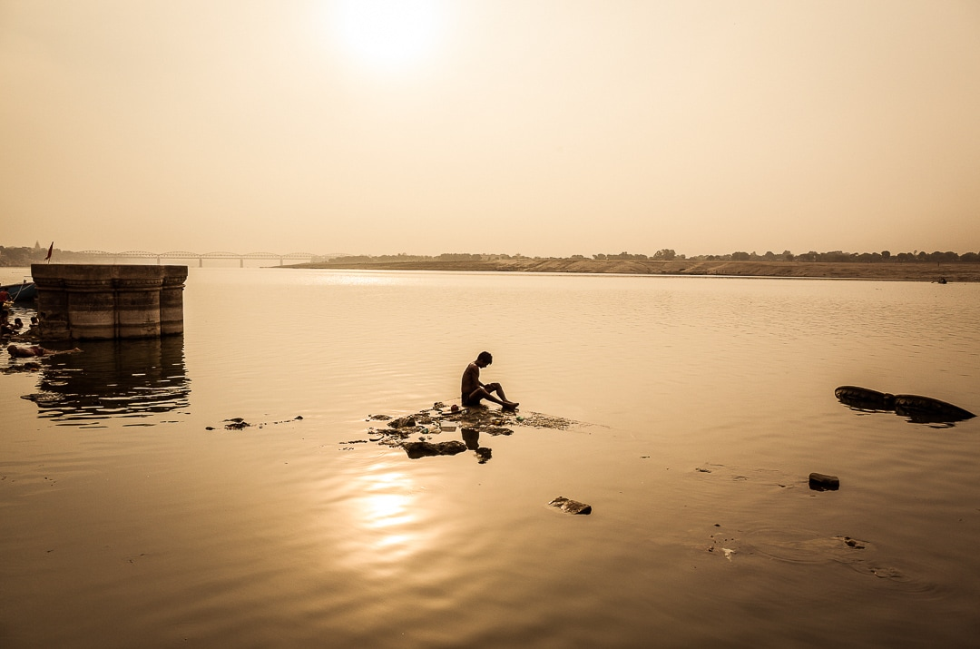A man bathes in the Ganges at sunrise in Kashi