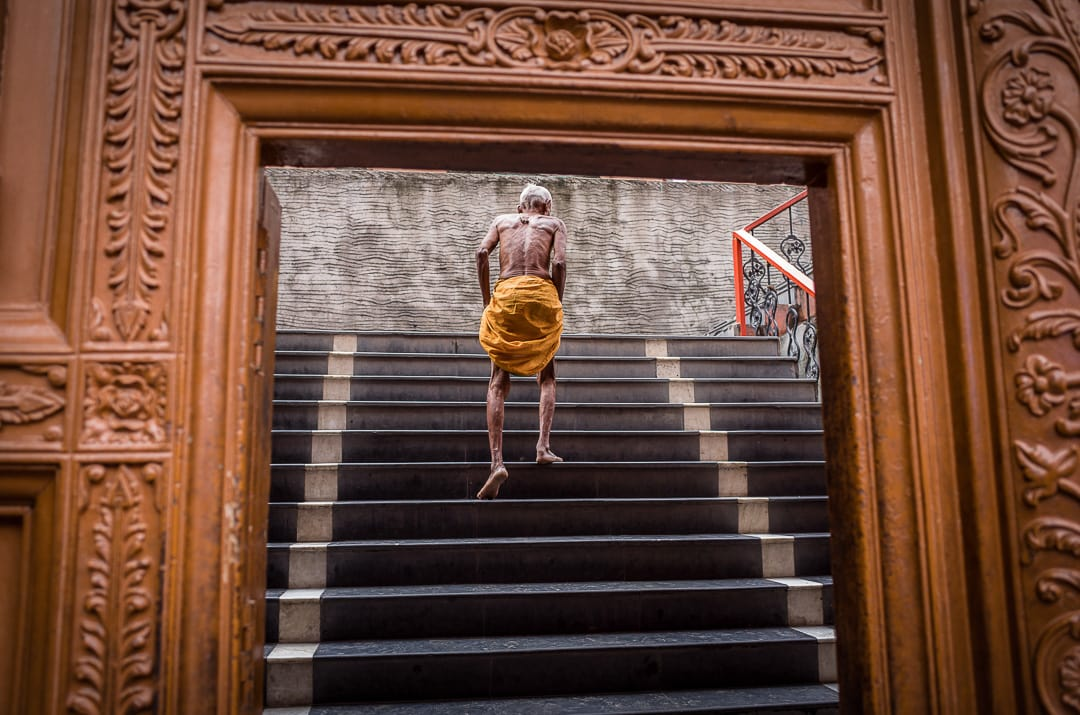 A thin old man in an orange doti climbs the stairs of a temple in Varnasi, India