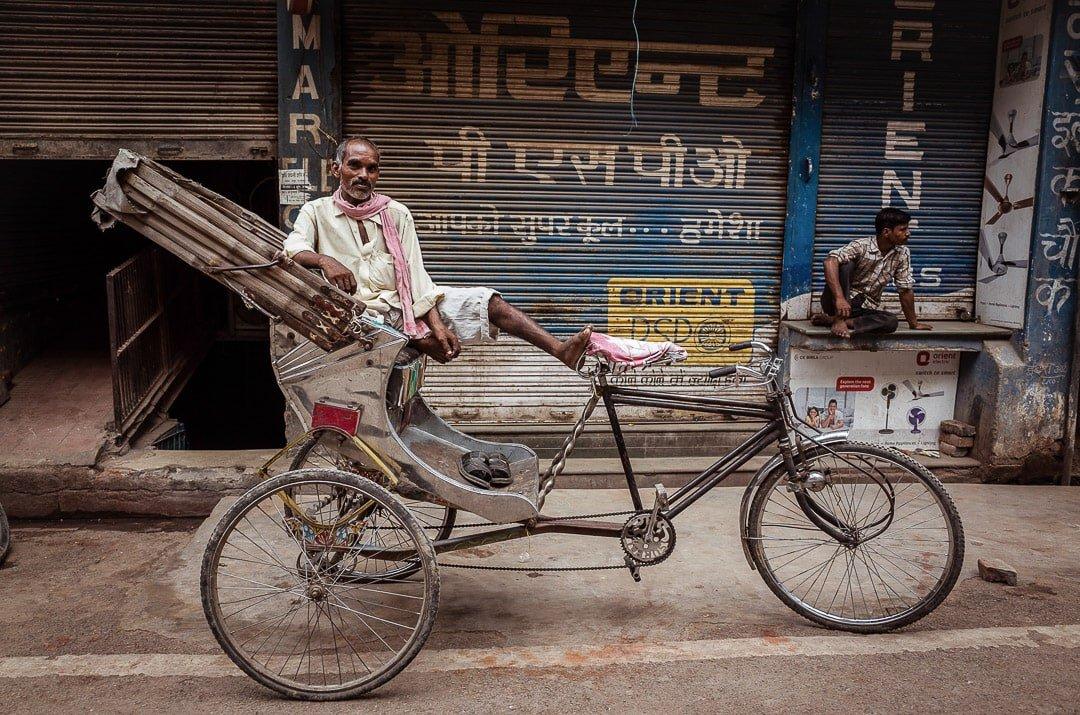 A rickshawala sits on a trishaw in Varanasi