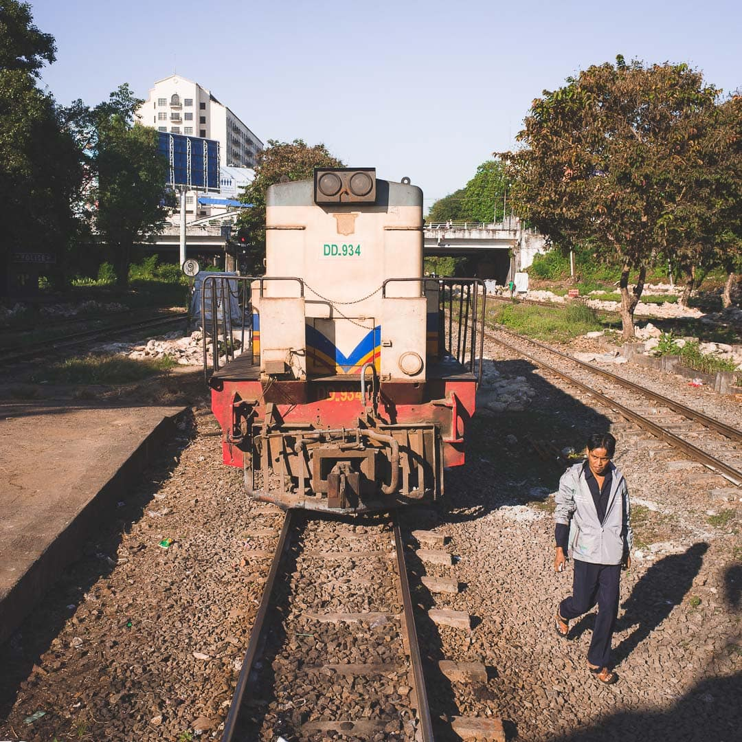 A man walks in front of the Yangon circle train at the Central Railway Station in Myanmar