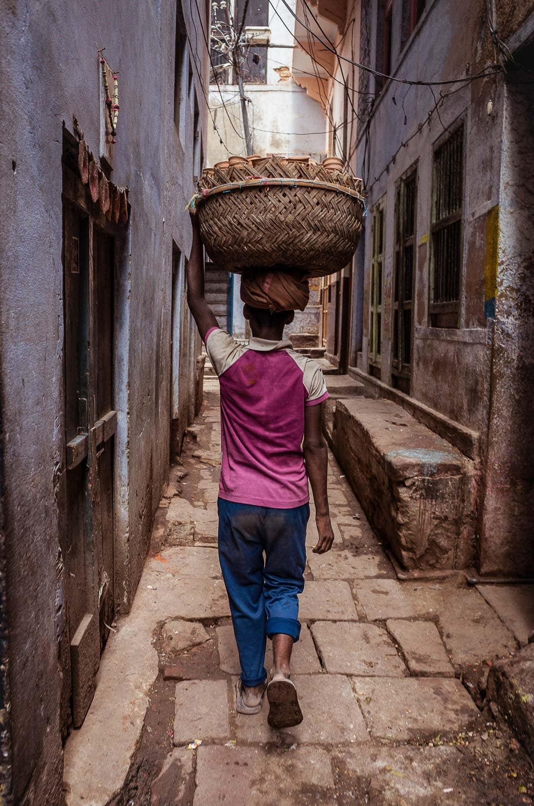 A young man carries chai cups in a basket on his head in Banares, India