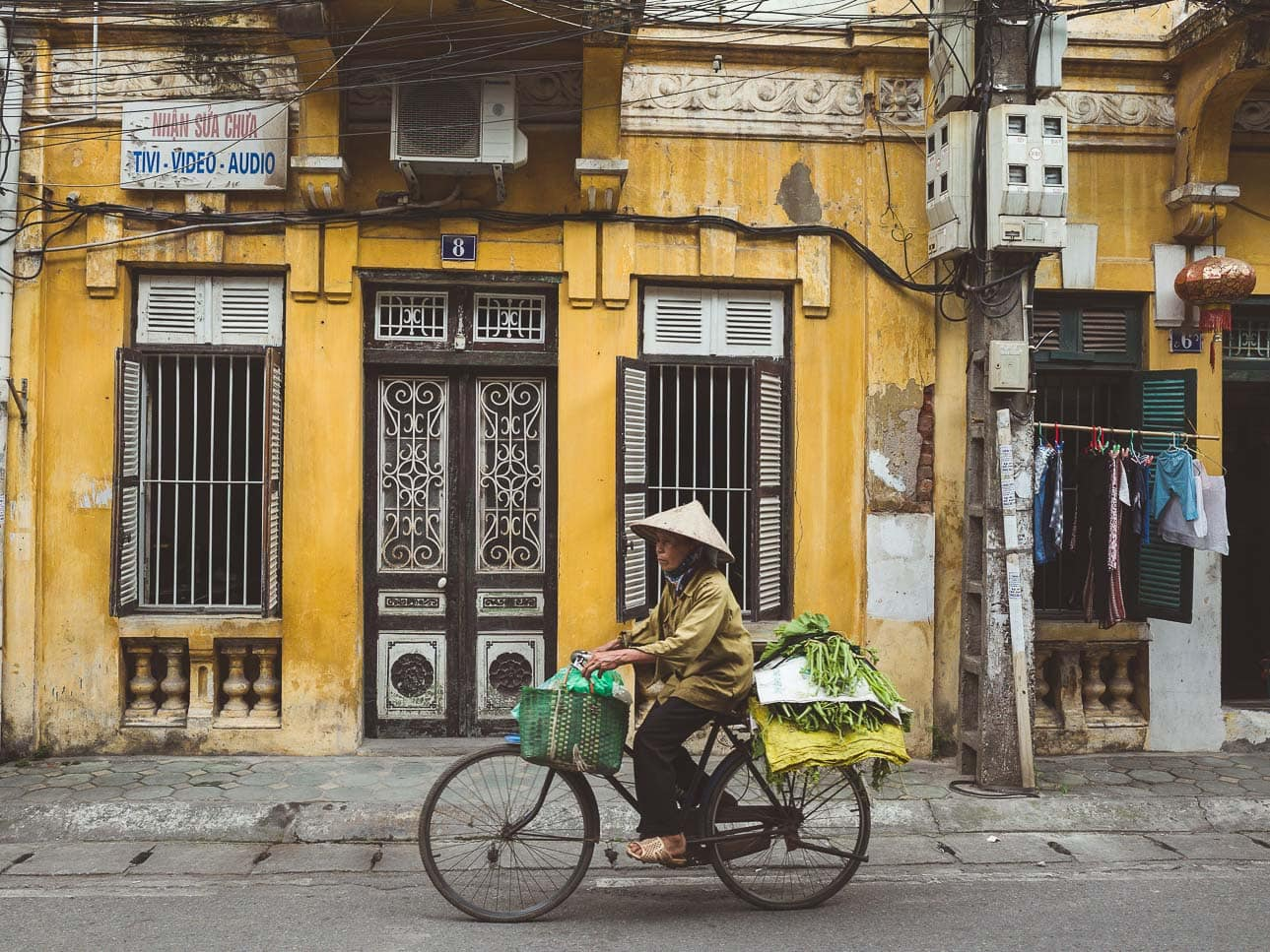 A woman wearing a conical hat rides her bicycle in front of a yellow home in Hanoi, Vietnam