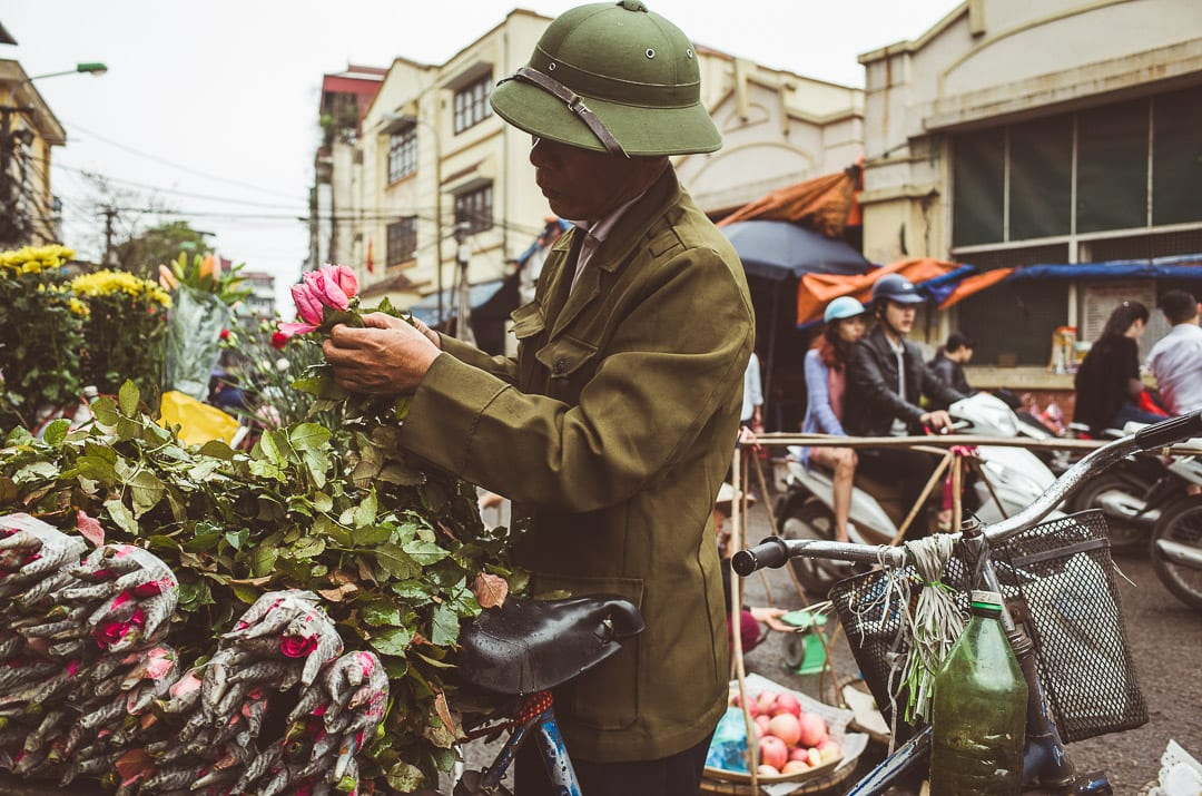 A flower salesman unties flowers near Dong Xuan market in Hanoi, Vietnam