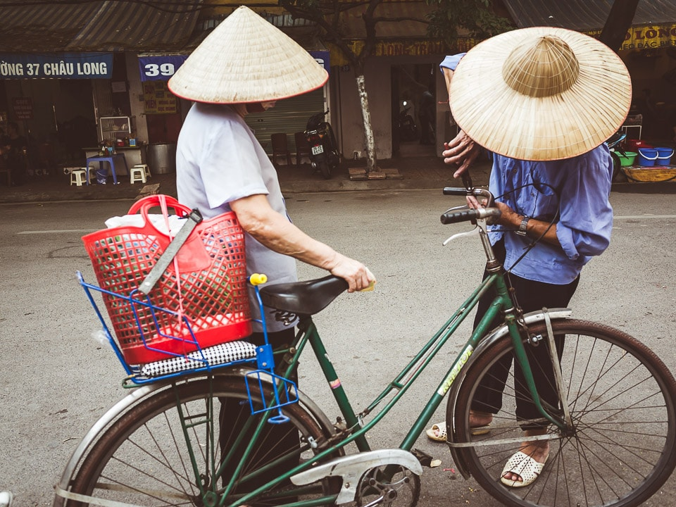 A bike mechanic helps a woman with her bicycle in Hanoi