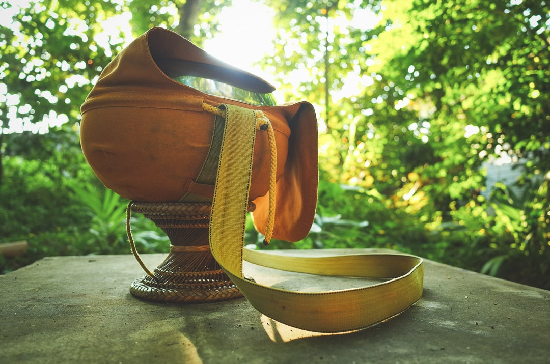 An orange Buddhist alms bowl with a strap on it at Wat Umong temple