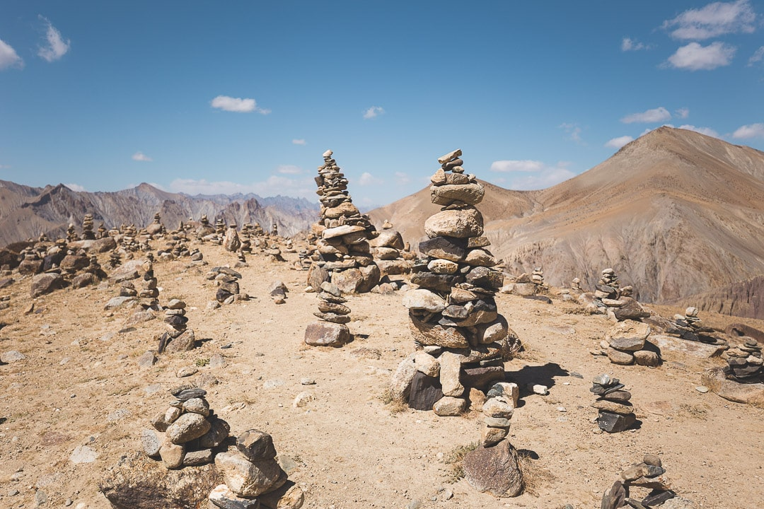 A smaller summit along the Markha Valley trek strewn with rocks and cairns in Ladakh