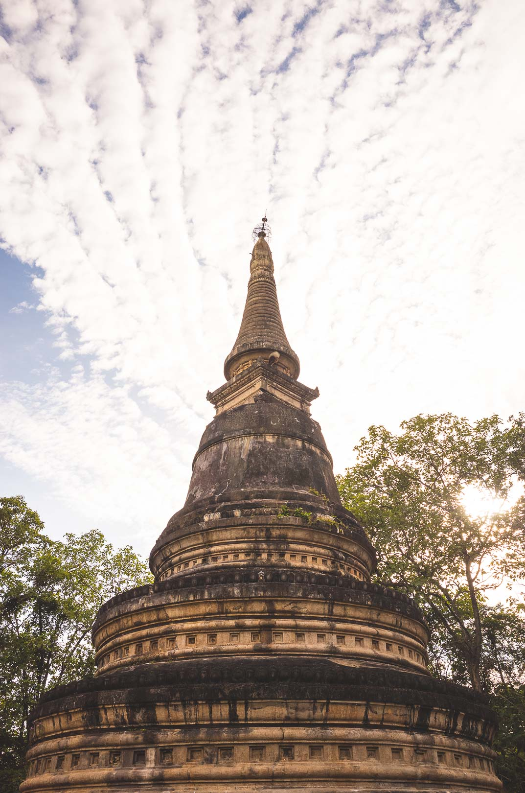 Looking up at the clouds and the large chedi at Wat Umong temple in Chiang Mai, Thailand