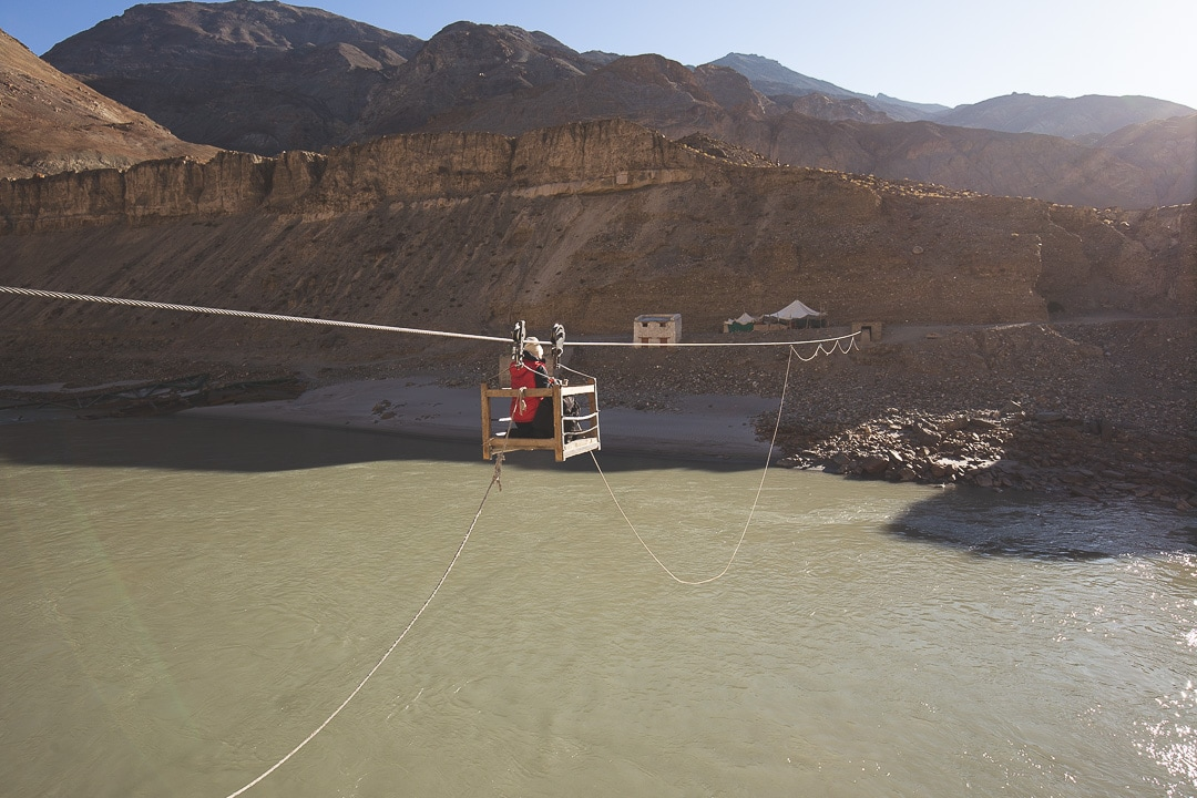 A woman uses a pulley cart across the Zanskar River in Ladakh, India